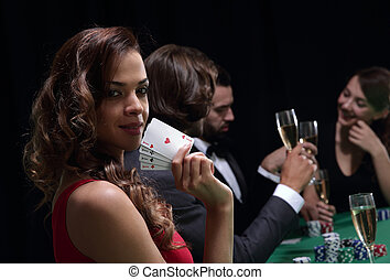 Woman at roulette table holding champagne glass in casino