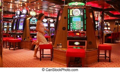 Woman at slot machine in play room in Persian Gulf. - ...