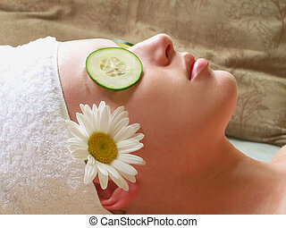 Woman lying down at spa with cucumber slices on her eyes, daisy and towel.