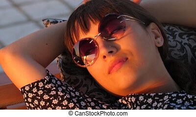 Woman at sunglasses resting at sunset