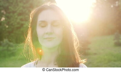 woman at sunset straightens hair. Slow motion.