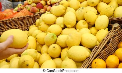 Woman at supermarket, choosing lemon, 4k, copy space