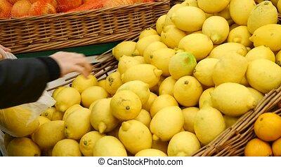 Woman at supermarket, choosing lemon, 4k, copy space.
