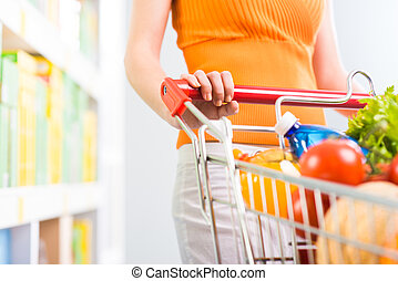 Woman shopping at supermarket, hands on trolley close-up.