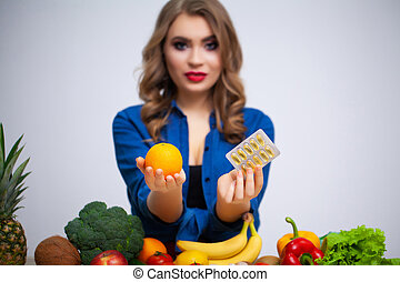 Woman at table holding orange and pills on fruit and vegetables background
