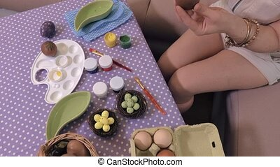Woman at table with Easter eggs decorations