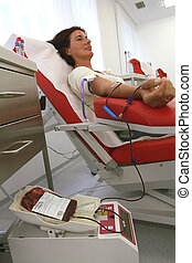 woman at the blood donation - a woman donates blood at a...