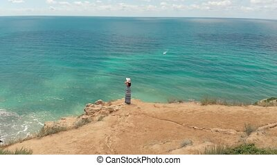 Woman at the edge of the cliff watching seascape - Woman...