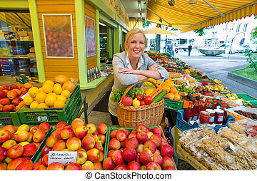 woman at the fruit market with shopping basket - a young...