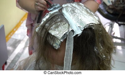 woman at the hairdresser,hair stylist dyes her hair.