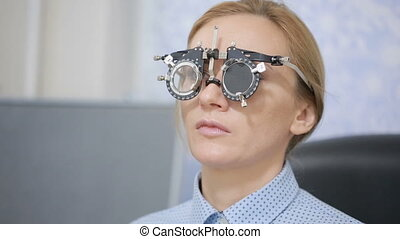 woman at the reception of an ophthalmologist. the selection of spectacle lenses