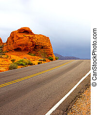 Woman at the road in Valley of Fire State Park in Nevada, ...