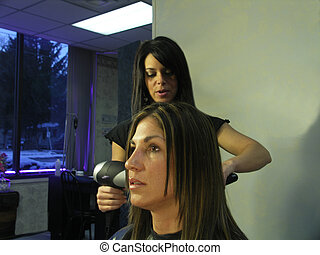A woman gets her hair colored at the salon.