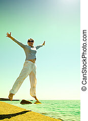 woman at the sea - woman jumping at the sea