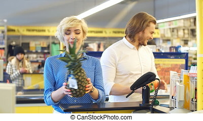 Woman at the supermarket checkout, she is paying using a credit card.