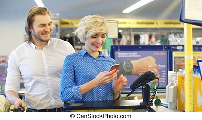 Woman at the supermarket checkout, she is paying using a...