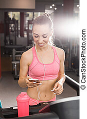 woman at the treadmill holding a phone