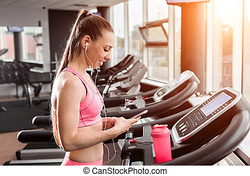 woman at the treadmill with a phone