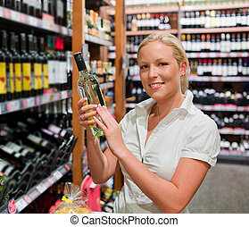 woman at the wine shelf of a supermarket