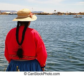 Woman in traditional Peru clothes at Titicaca lake floating islands