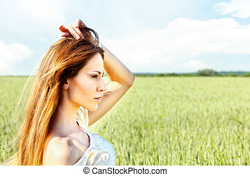 Woman at wheat field on sunny day