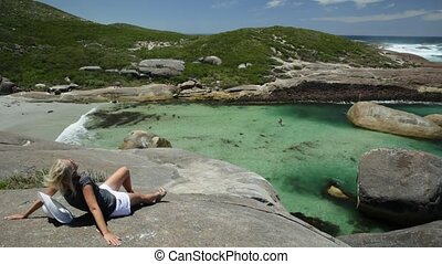 Woman sitting on the cliffs above elephant-shaped rocks of Elephant Rocks in Denmark, Western Australia. Happy tourist looking Great Southern Ocean in William Bay NP. Summer destination in Australia.