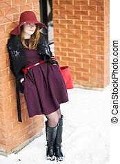 Woman at winter day near brick wall