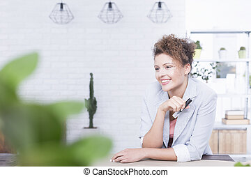 Woman at work - Young pretty smiling woman at work in a...