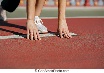 Woman athlete at starting position ready for the race. Empty space