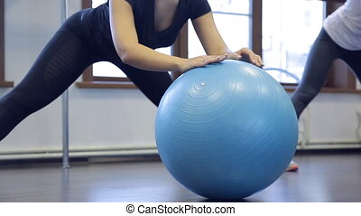 Woman athlete doing exercises on gym ball in fitness studio....