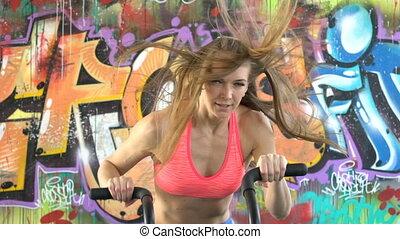 woman athlete doing intense workout on gym bike.