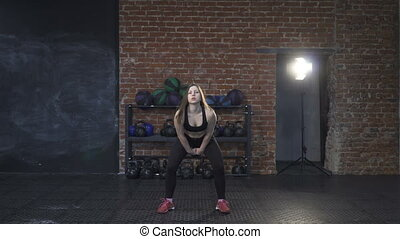 Woman athlete doing kettlebell swings in the cross-fit gym