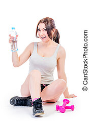 woman athlete holding a bottle of water and smiling
