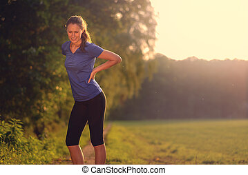 Woman athlete pausing to relieve her back pain holding her hand to her lower back with a grimace while out training in the countryside with copyspace
