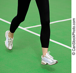Woman Athlete Runner Feet Running on Green Running Track. Fitness and Workout Wellness Concept.