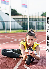 woman athlete stretching on racing track before running