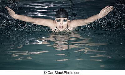 Woman athlete swimming butterfly stroke in pool.