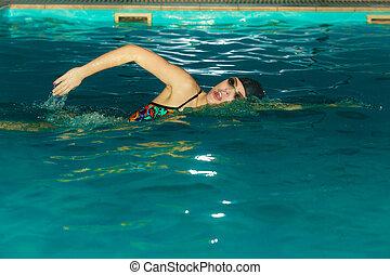 Woman athlete swimming crawl stroke in pool.
