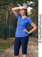 Woman athlete wiping sweat from her forehead