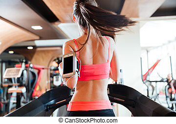 Woman athlete with balnk screen smartphone running on...
