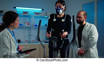 Woman athlete with mask doing fitness exercises in science sport lab with electrodes attached while scientist holding tablet supervising whole process. Physician using notepad controling EKG data