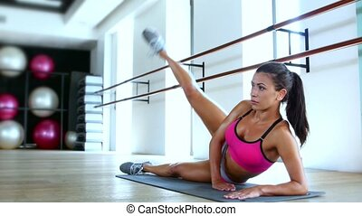 Woman athlete working out kneeling on a gym mat raising her...