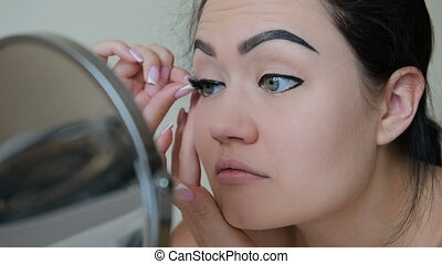 Woman attach false eyelashes to herself in slow motion HD -...