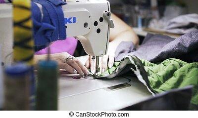 Woman attaching a zipper to a vest