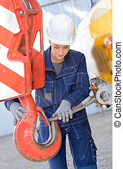 Woman attaching metal wire to hook of crane