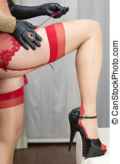 woman attaching stockings to the garter belt