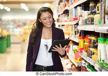 woman, aussieht, an, digital tablette, in, shoppen, kaufmannsladen