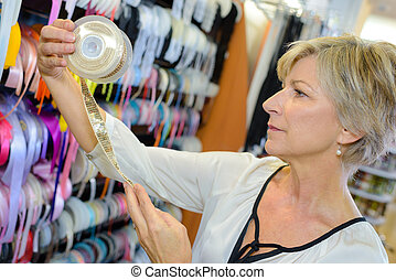 woman, aussieht, an, spule, von, geschenkband, in, handwerkspeicher