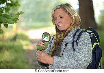 woman, aussieht, durch, vergrößerungsglas