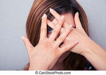 woman, aussieht, kamera, durch, finger
